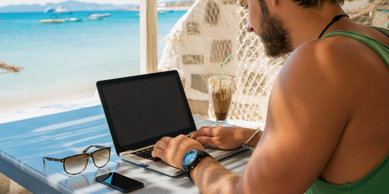 Man with laptop by the beach